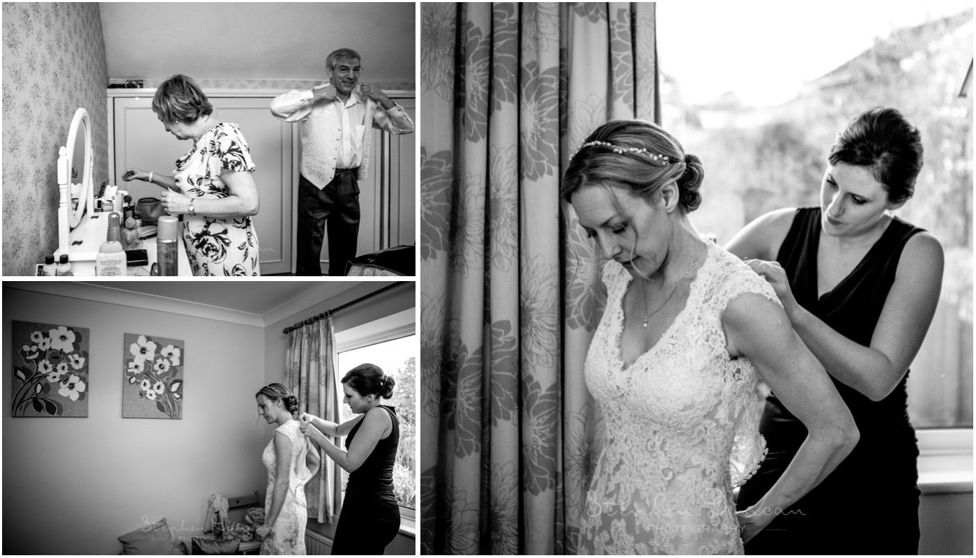 Romsey Abbey wedding photographer bride gets into wedding dress