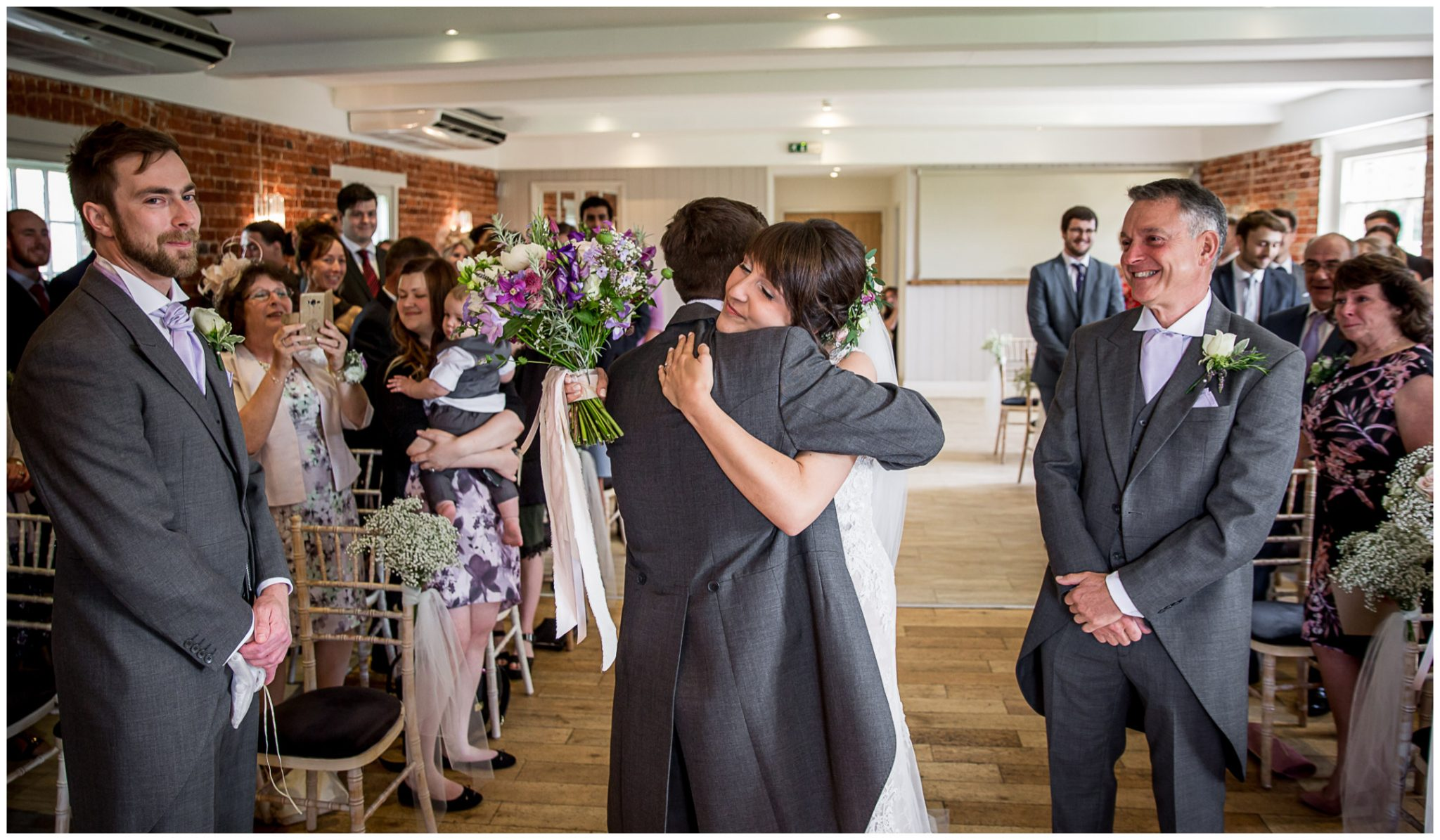Sopley Mill wedding photography bride hugs groom as they see each other for first time that day