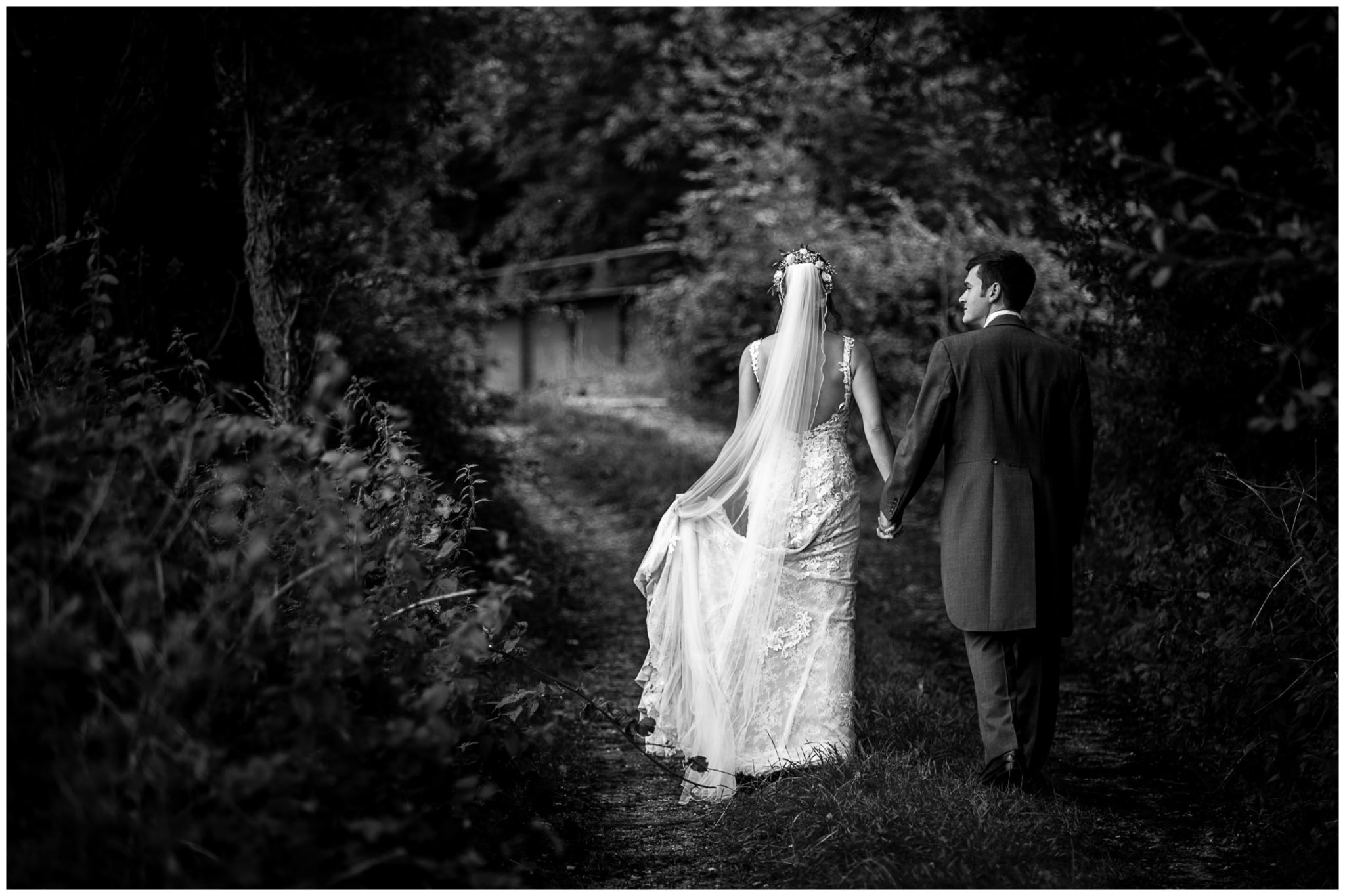 Sopley Mill wedding photography black and white photo of couple walking towards bridge