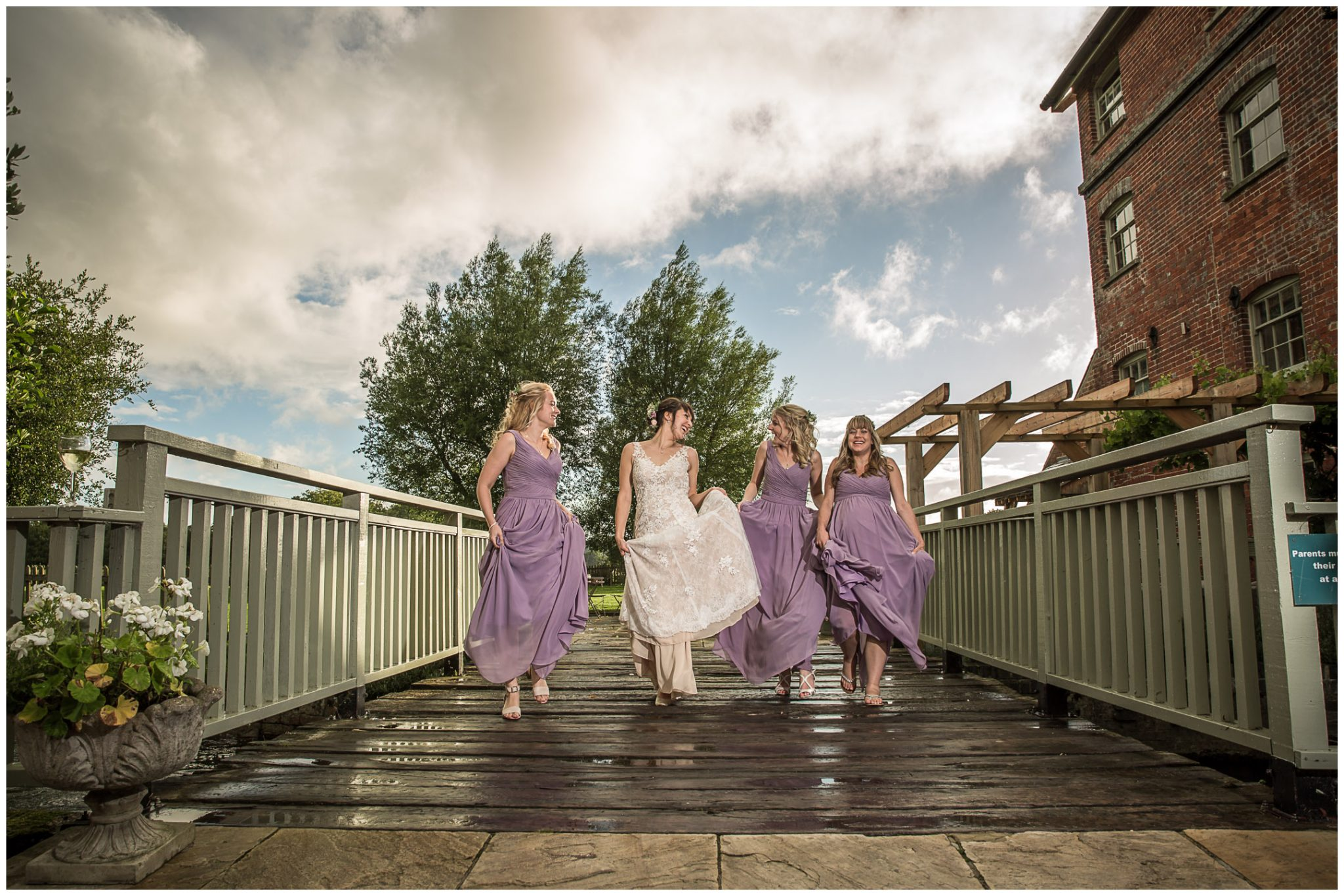 Sopley Mill wedding photography bride with bridesmaids on bridge