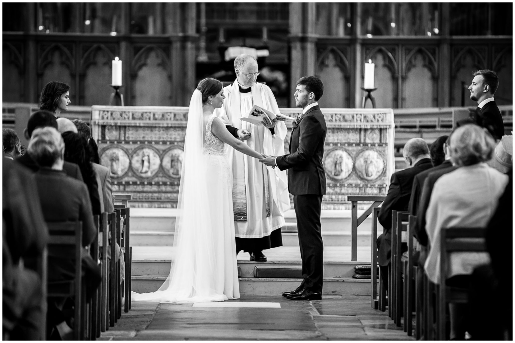 winchester cathedral wedding photography bride and groom hold hands black and white