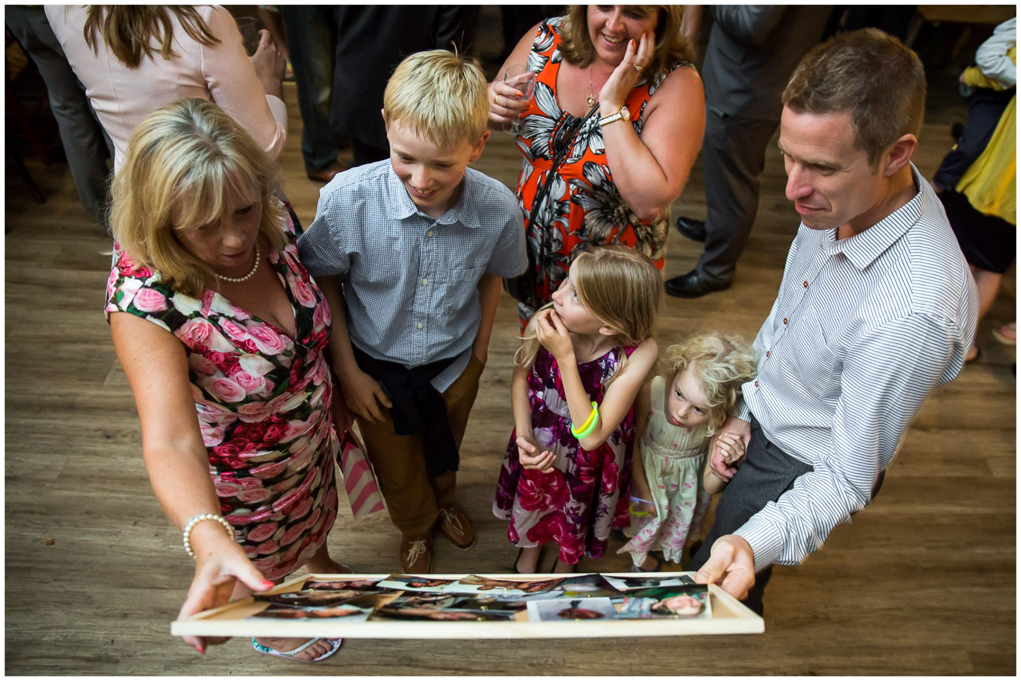 Winchester Great Hall wedding photography guests looking at photos of groom