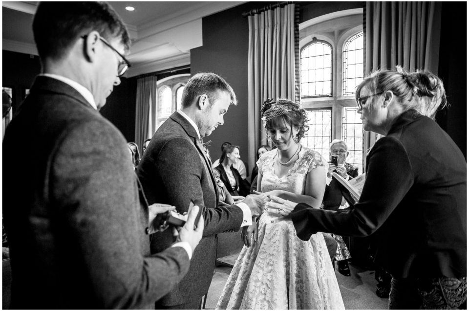 Castle Room Winchester wedding photography groom puts ring on finger