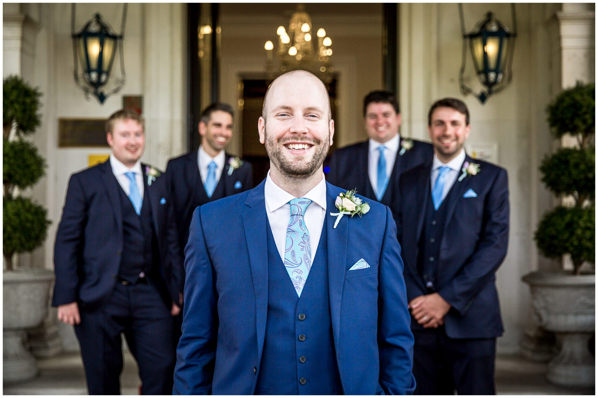 Oakley Hall wedding photography groom with groomsmen at venue entrance