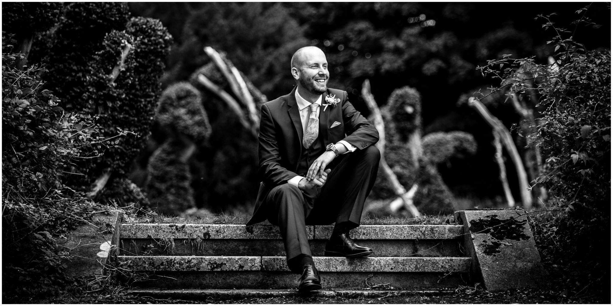 Oakley Hall wedding photography groom portrait sat on steps