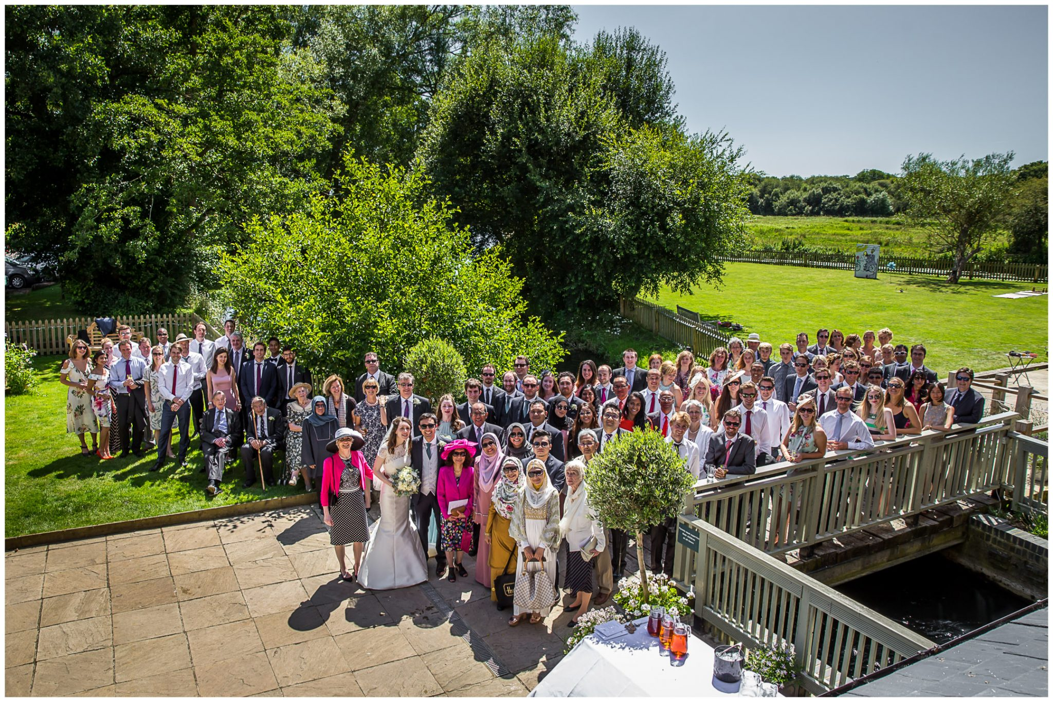 Sopley Mill Summer wedding large group photo by the river