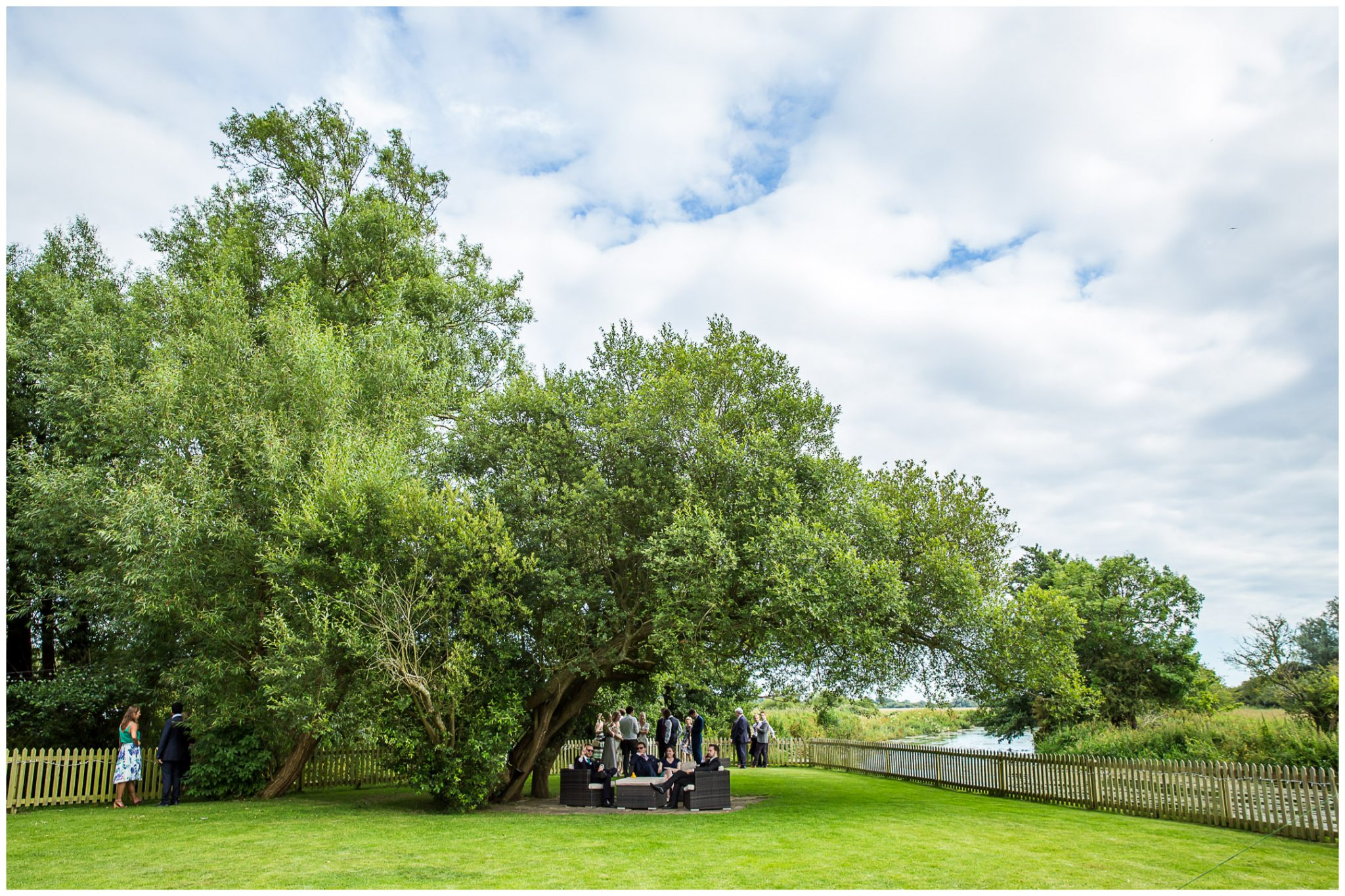 Sopley Mill Summer wedding sitting in the shade of the trees by the river