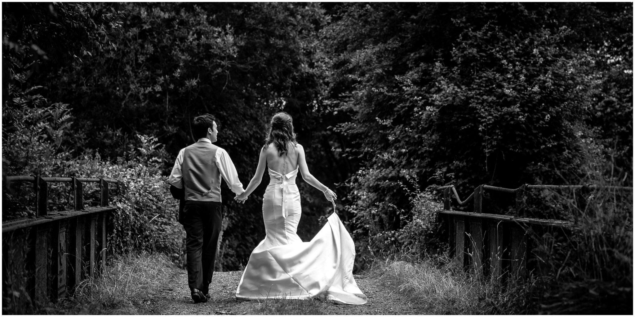Sopley Mill Summer wedding couple walk across iron bridge