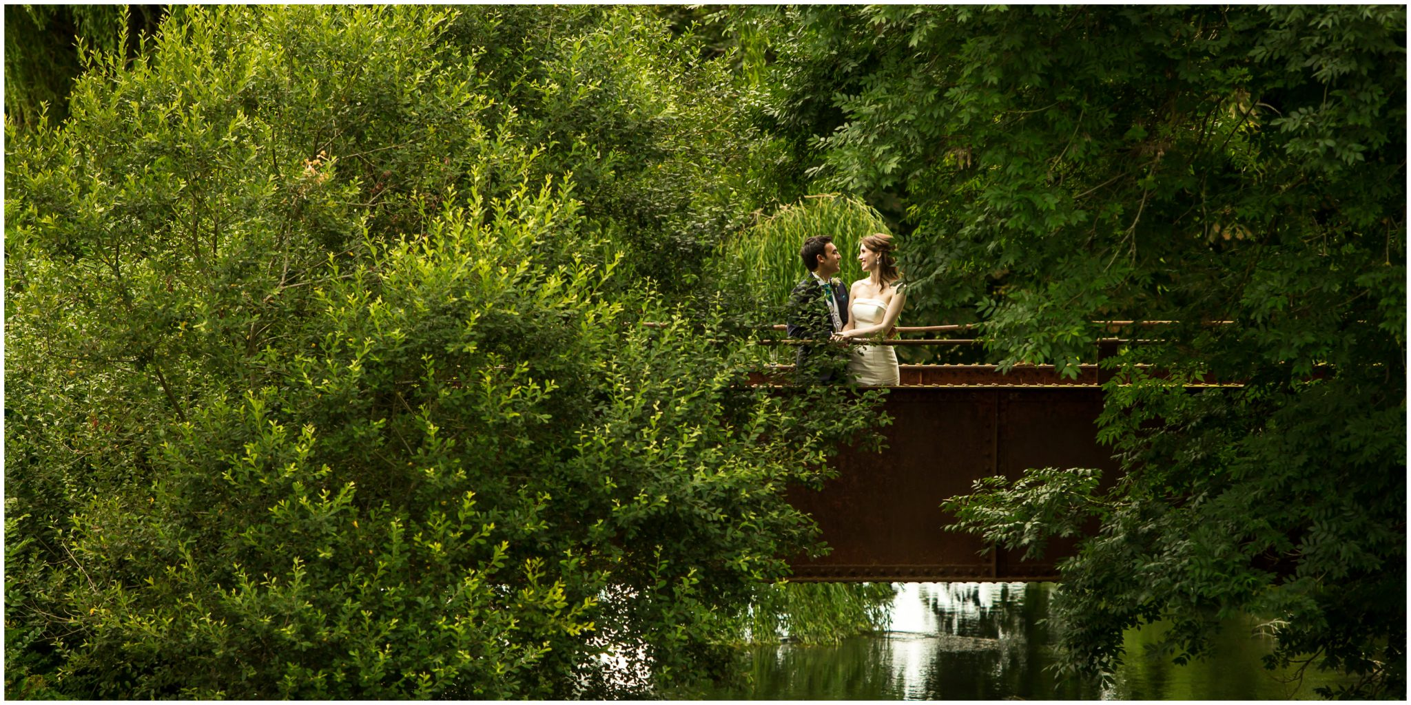 Sopley Mill Summer wedding couple stood on iron bridge