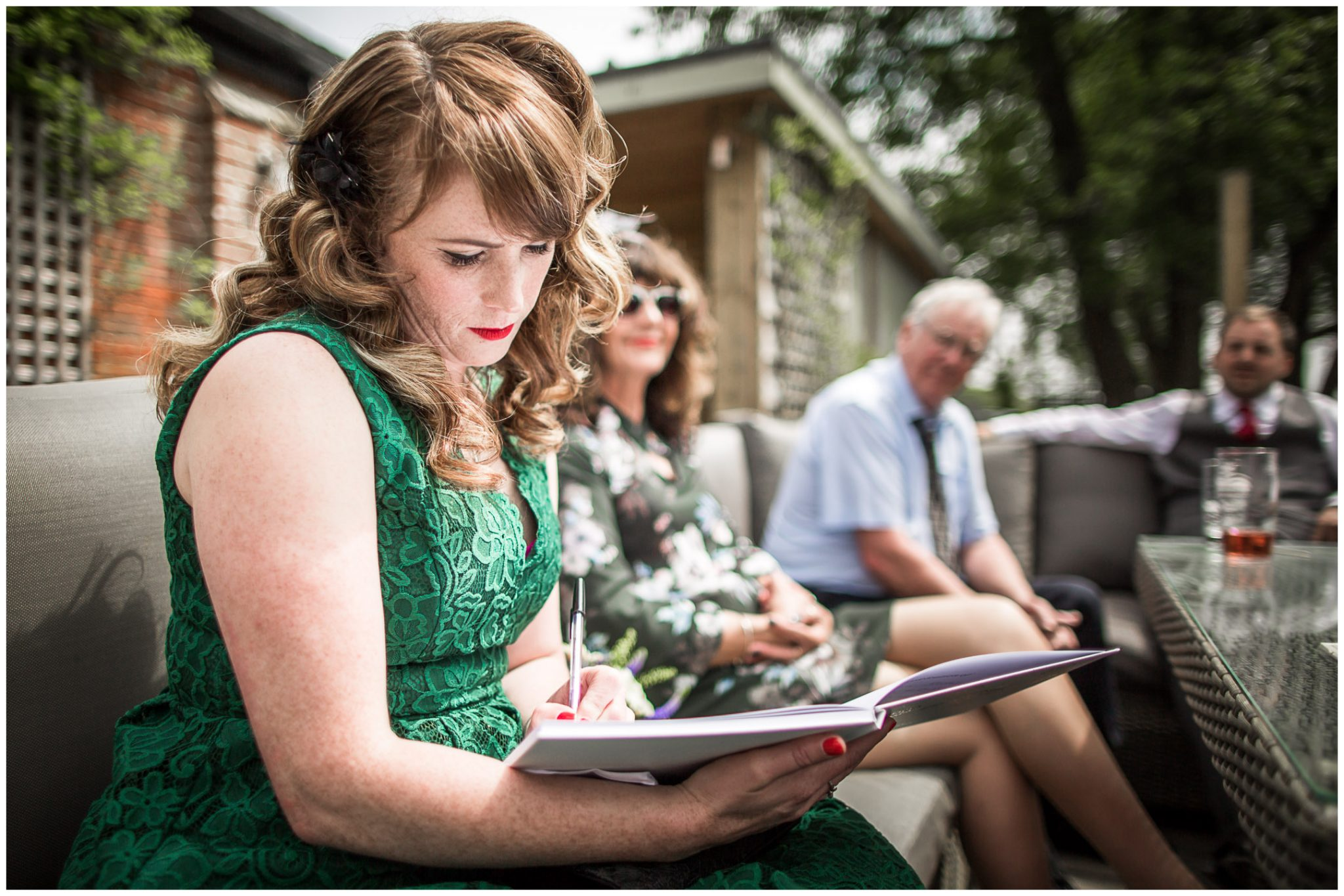 Bridesmaid writes in signing book during drinks reception