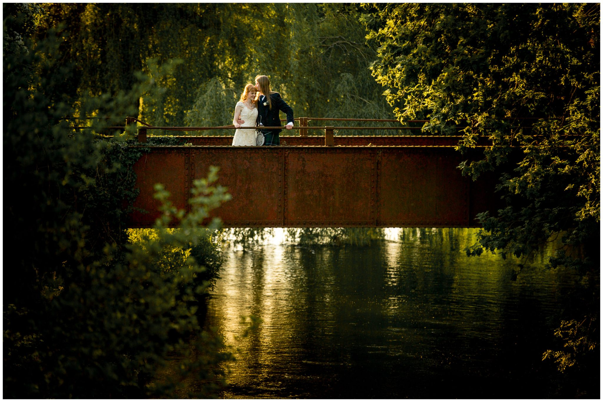 Bride and groom in evening light on bridge behind wedding venue