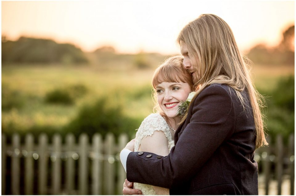 Couple portrait in golden evening light with view across water meadows