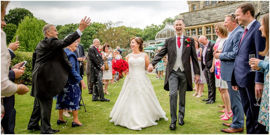 Couple received by guests with confetti in gardens