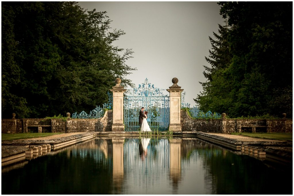 Couple portrait by blue gates at the end of the pond