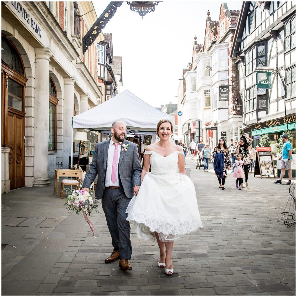 Couple waling along High Street in wedding clothes