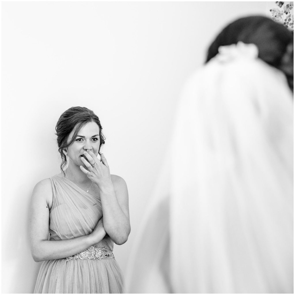 Bridesmaid reacts to bride in dress