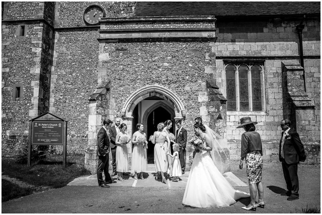 Black and white photo of bride preparing to enter church at start of the wedding ceremony