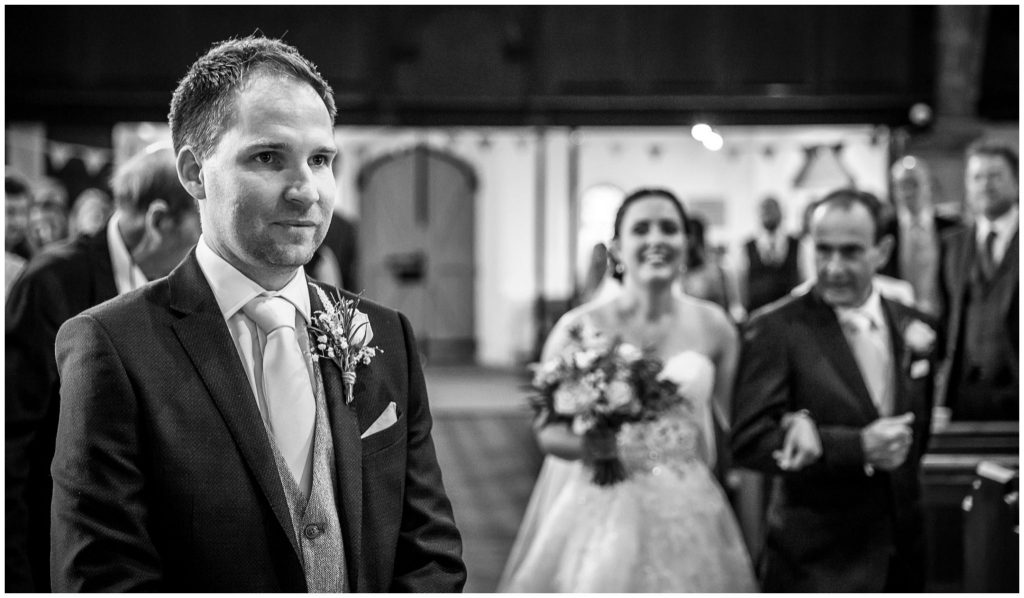Groom stood at front of the aisle as bride arrives