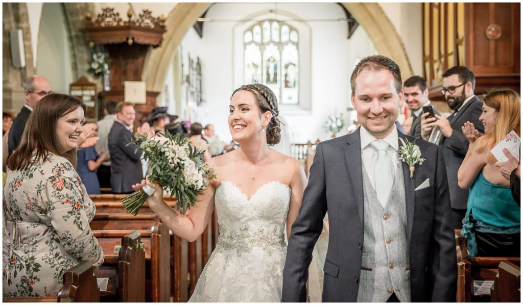 Couple smiling as they walk down the aisle