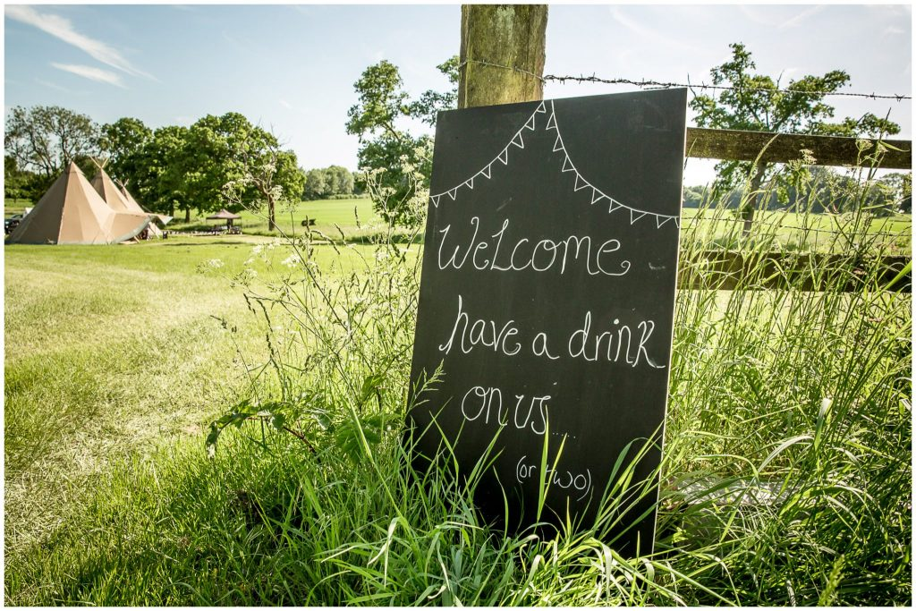 Welcome sign at reception venue - tipi in a field