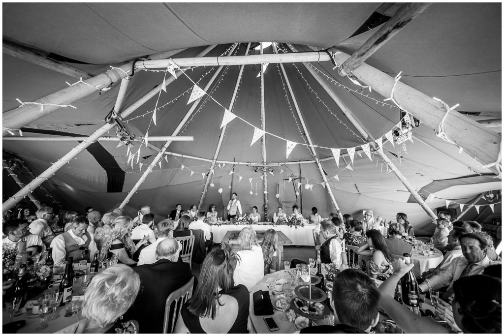 Black and white wide photo of marquee interior during speeches with groom stood at the top table
