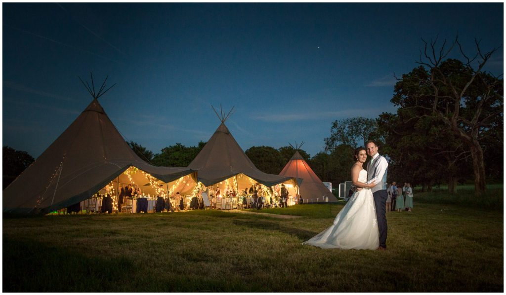 Couple colour portrait outside reception marquee at dusk