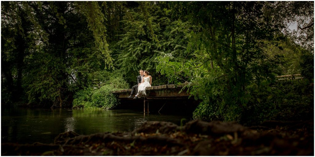 Bride and groom sitting on bridge across a river