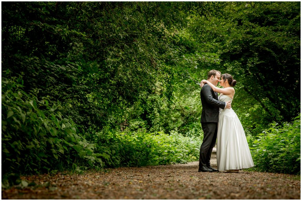 Bride and groom face each other on path through the woods