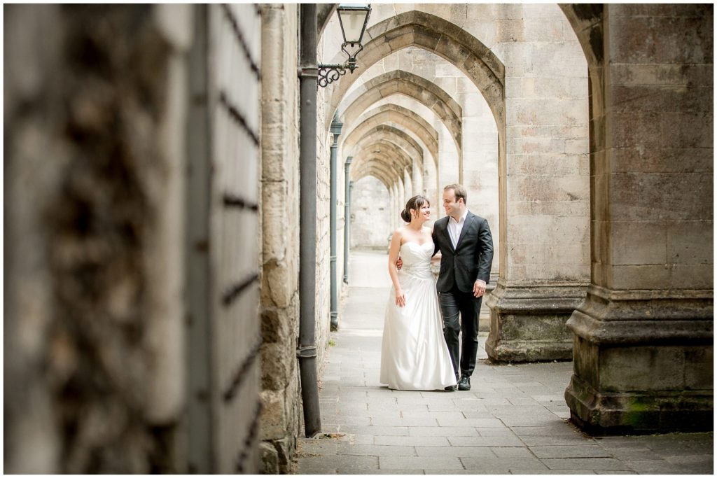 Bride and groom walk through cloisters