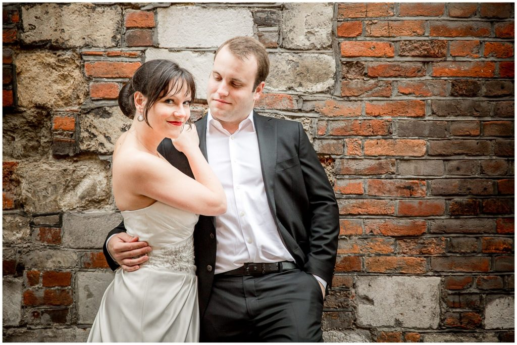Couple pose against wall brickwork