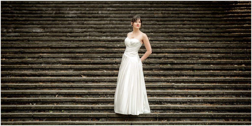 Bride pose in wedding dress on Law Court steps in Winchester
