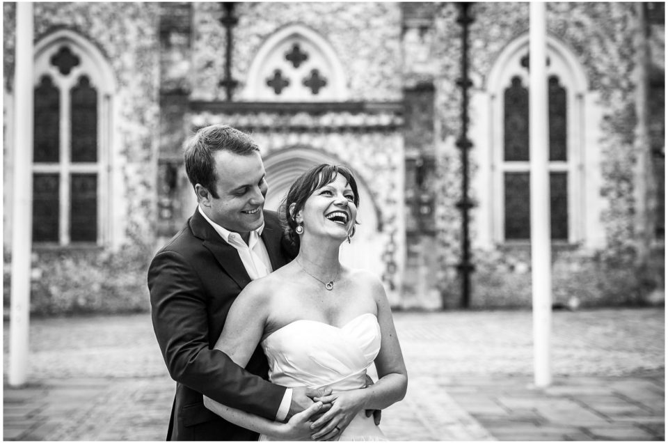 Black and white portrait photo with wedding couple laughing