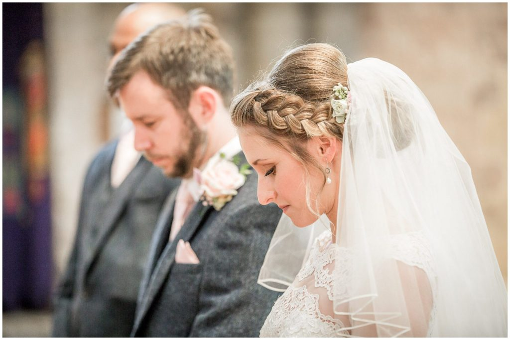 Bride and groom bow heads at start of marriage service at Romsey Abbey
