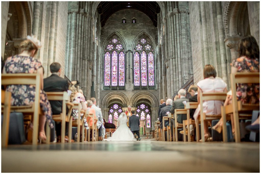 The couple kneel to receive the blessing of their marriage