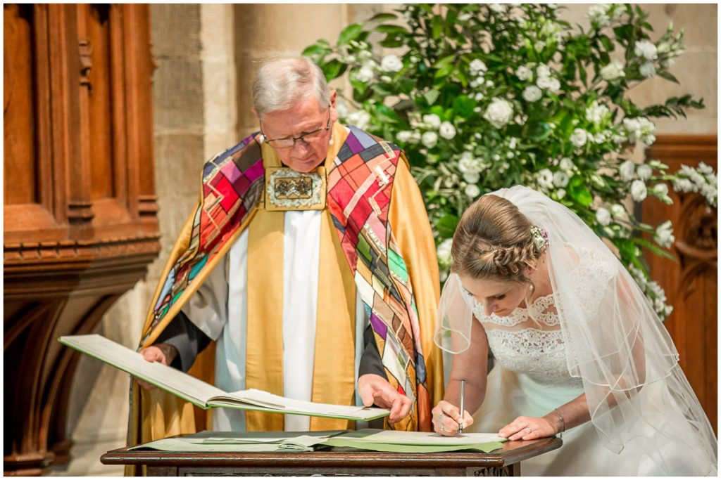 Bride signs marriage register at Romsey ABbey