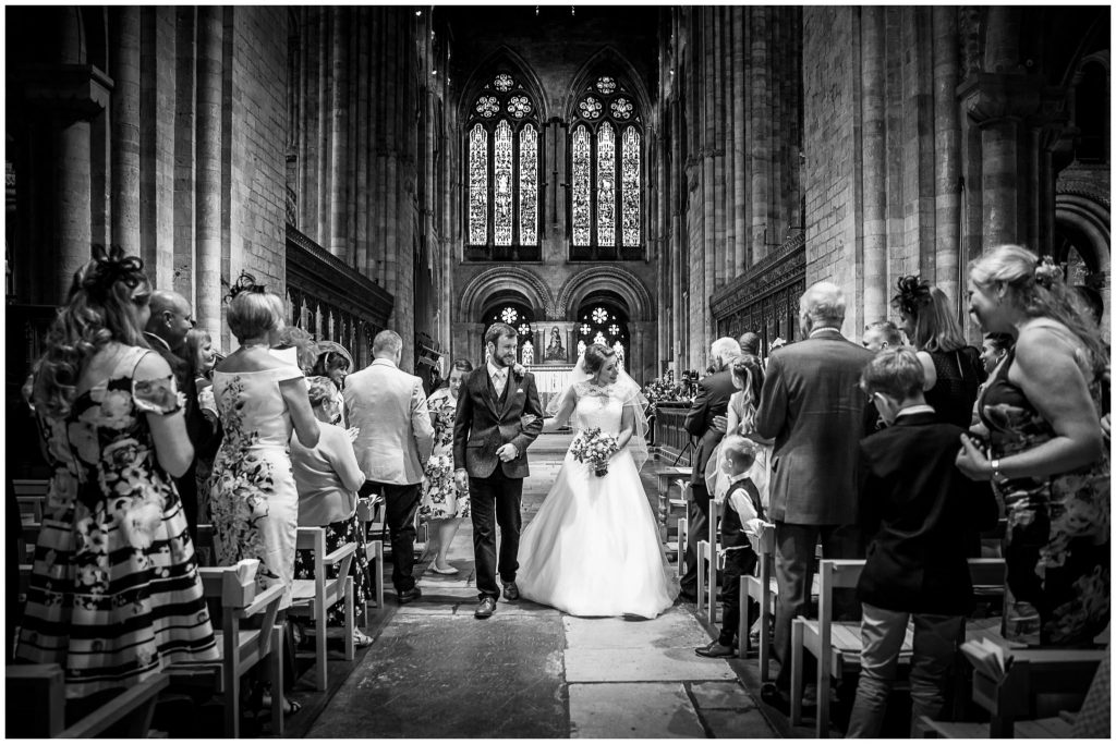 Bride and groom walk down the aisle at Romsey Abbey