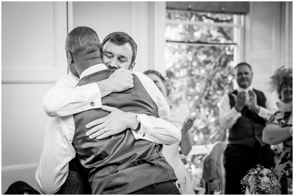 Groom and best man hug after speeches