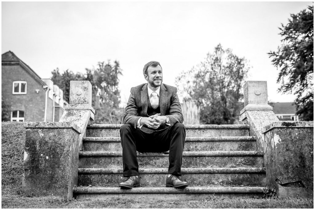 Portrait of groom sat on steps