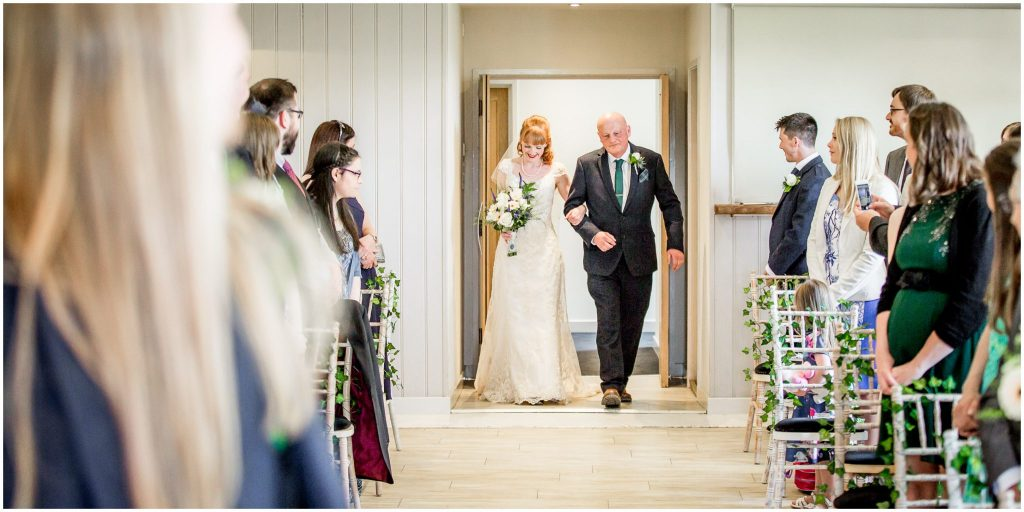 The bride walks through the door on her father's arm