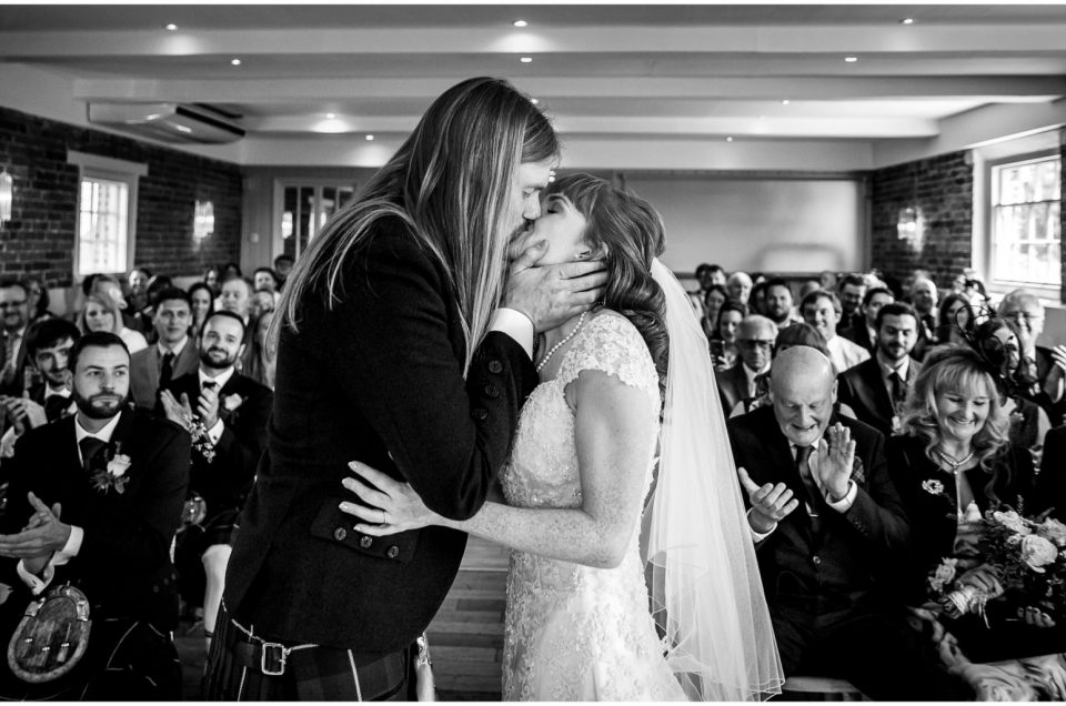 Awesome kiss! Newly married couple black and white as guests applaud