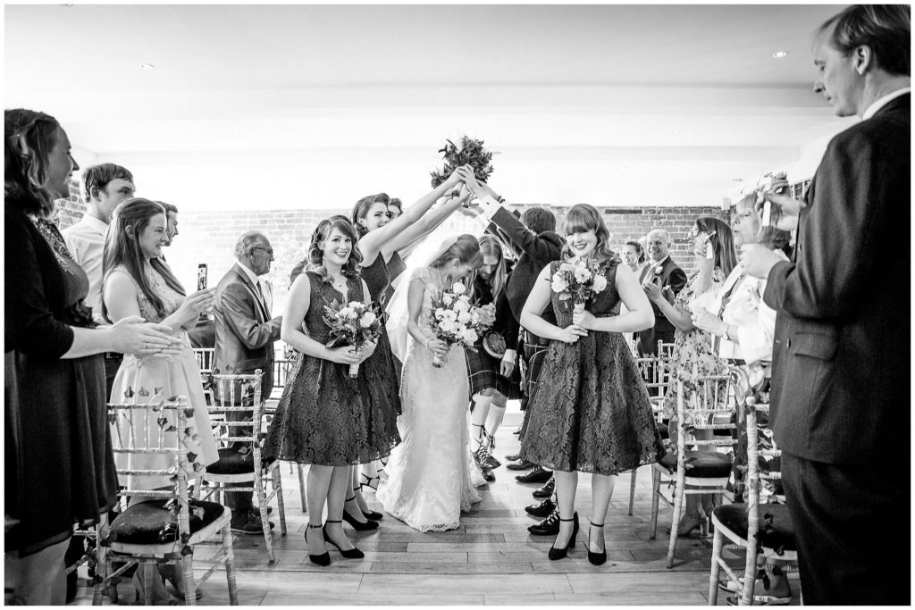 Couple walk down the aisle to a floral arch