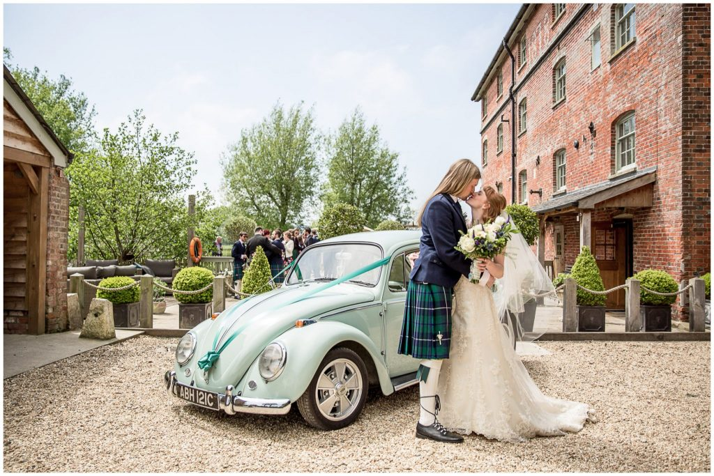 Couple kiss in front of VW Beetle wedding car