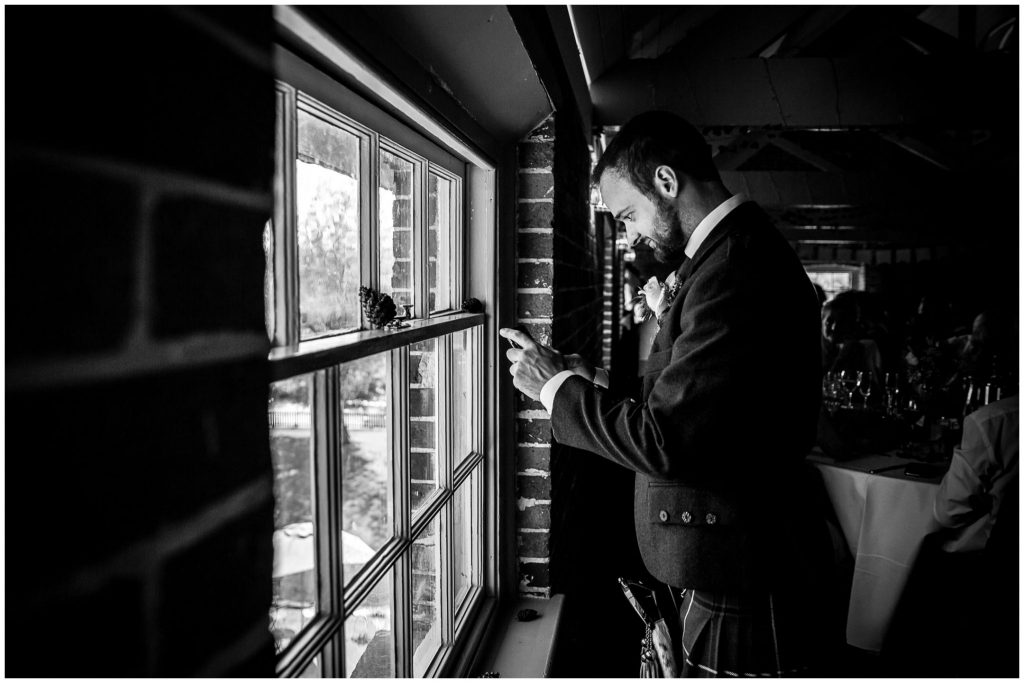 Groomsman taking a photo of the view from the third floor window