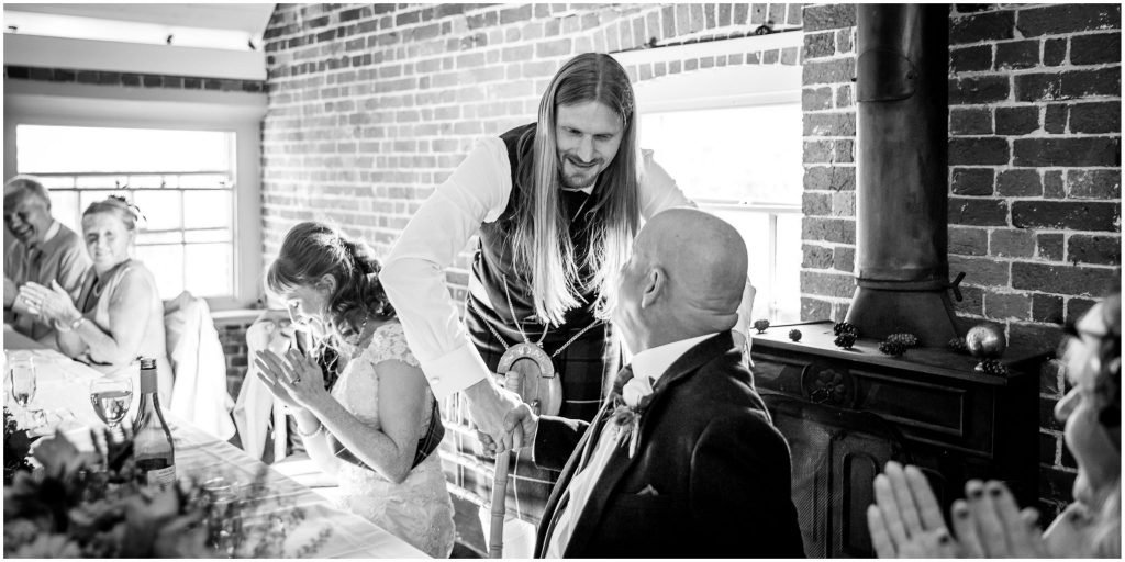 Groom and father of the bride shake hands during speeches