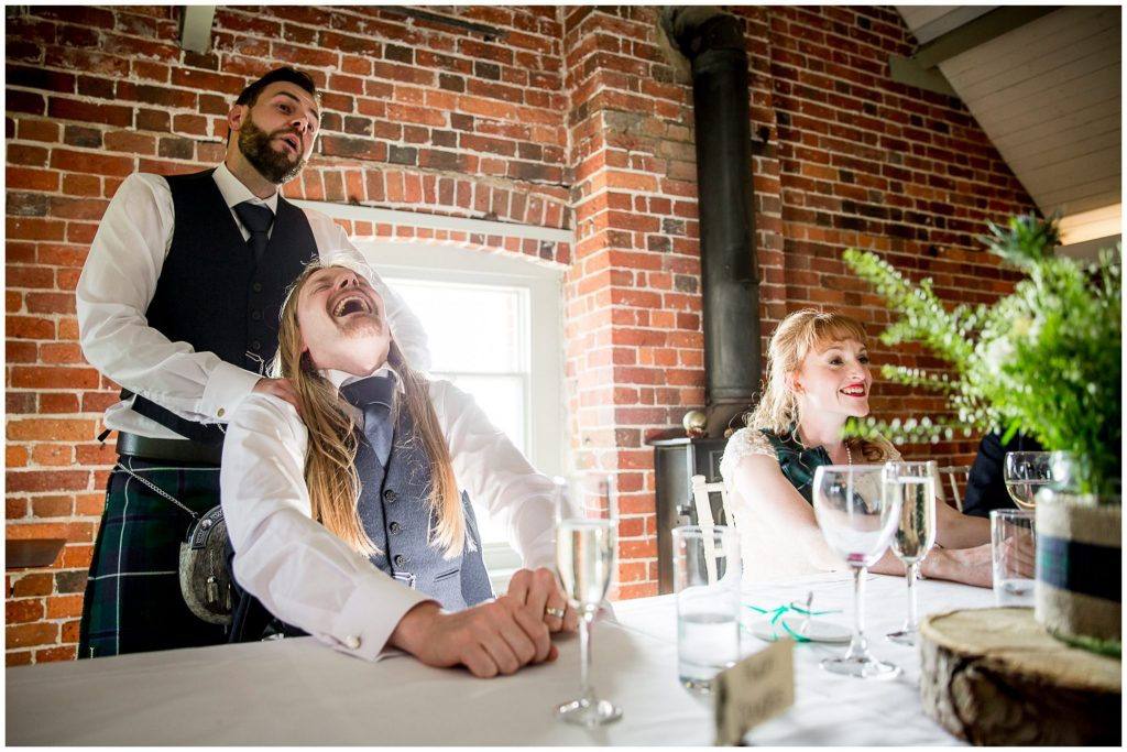 Groom laughing at best man's speech