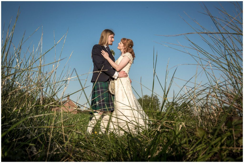 Couple posing in the water meadows with the Mill in the background