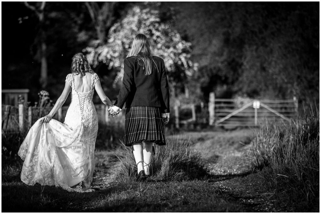 Couple walking away from camera holding hands black and white portrait
