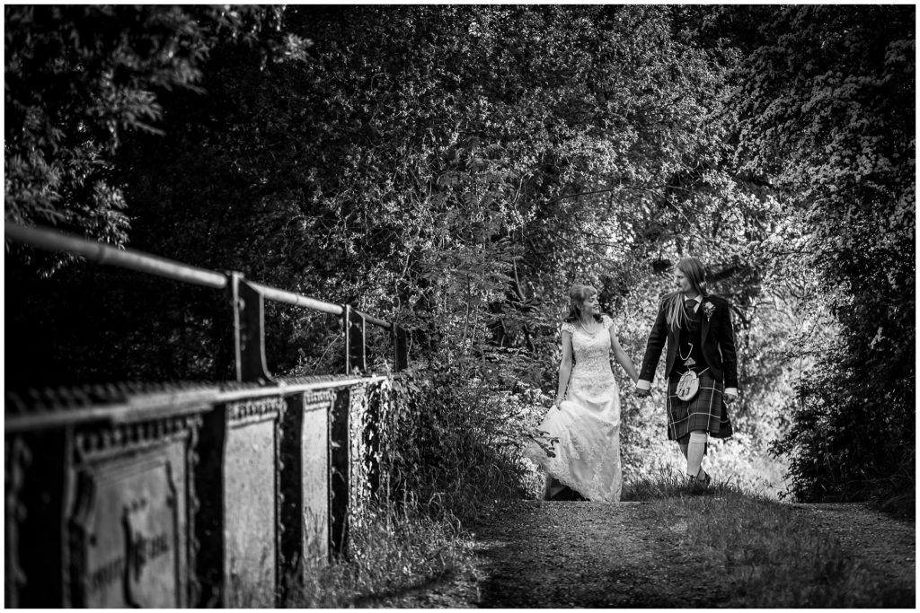 Black and white portrait of couple holding hands and crossing bridge