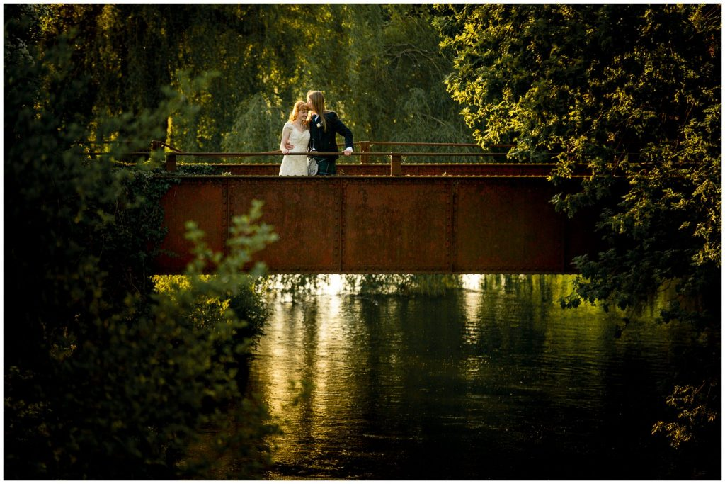 Bride and groom kiss on the bridge as the sun sets
