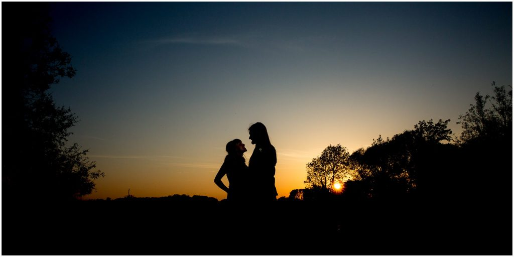 Couple silhouette with sunset over the water meadows